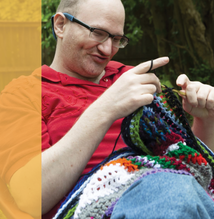Photo of Brandon Cantrell knitting in a chair.