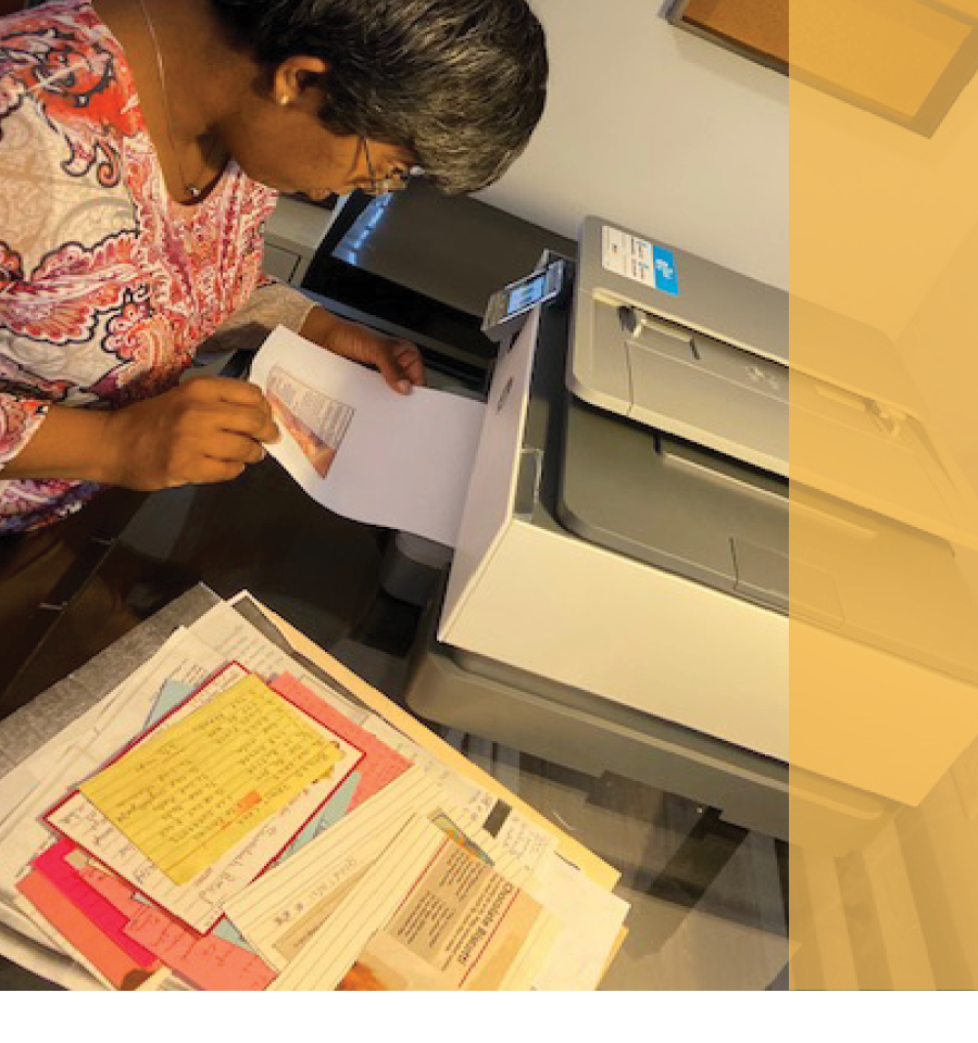 Nandi Isaac is sitting at her desk printing documents.