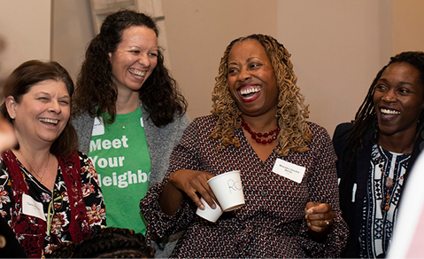 4 women standing next to each other smiling & laughing.