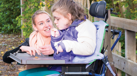 Photo of a Direct Support Professional with her client, who is a wheelchair user.